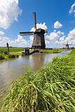 Dutch windmill in a fresh green field in summer with a blue sky