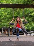 Smiling girl on swing in autumn park