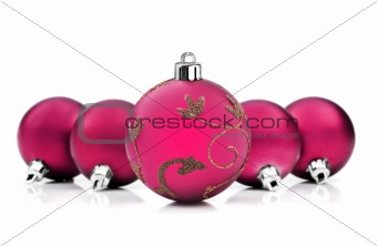 Bright pink christmas baubles on white background with space for text