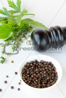 black pepper in a bowl and herbs thyme, basil