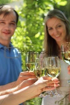 Celebration. People holding glasses of white wine making a toast
