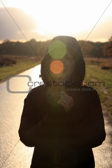 Asian woman stands in morning sunshine