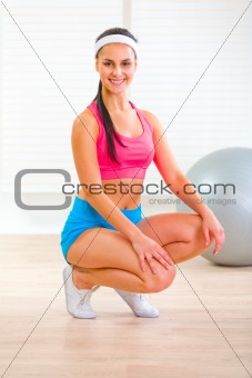 Smiling fit pretty girl squatting down