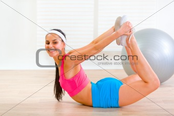 Smiling flexible girl making gymnastics exercise