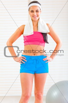 Happy fitness girl with towel around neck