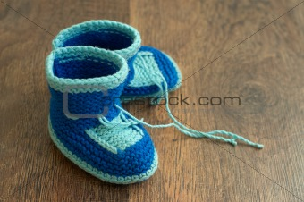 Knitted handmade baby's bootees on wood floor