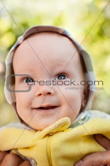 Happy baby boy on mother hands looking up