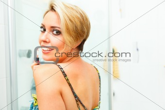 Smiling girl in bathroom applying lip gloss