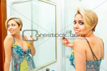Attractive girl in bathroom applying lipstick