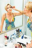 Attractive woman in bathroom applying mascara