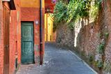 Narrow street among house and wall in Portofino.