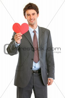 Smiling modern businessman with Valentin heart in hand