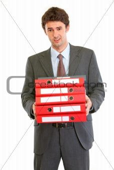 Displeased modern businessman holding many folders