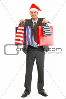 Smiling businessman in Santa hat giving shopping bags