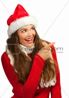 Beautiful woman in Santa hat pointing at copyspace