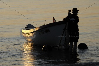 The fisherman near a boat during sunset