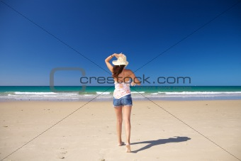 walking holding on straw hat at beach