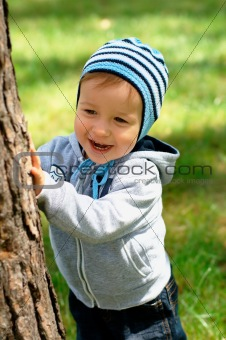 Baby hiding behind a tree