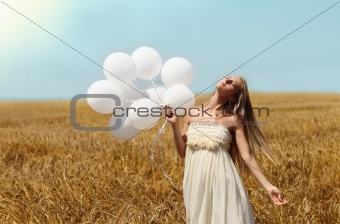Blond girl in the summer field