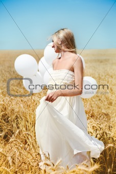 Beautiful girl with white balloons in the field