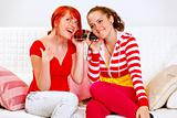 Sitting on sofa two pretty girlfriends holding headphones and listening music