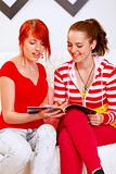 Cheerful girlfriends sitting on sofa and looking fashion magazine