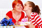 Girl presenting gift to her girlfriends and kissing her