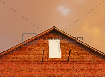 Fragment of brick house in the background reddish thunderclouds.