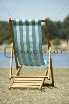 Lone Beach Chair Sitting Next To Water