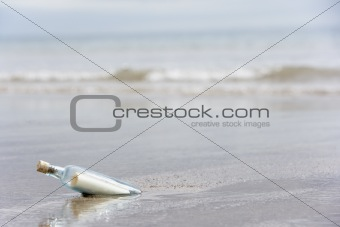 Message In A Bottle Buried In Sand On The Beach