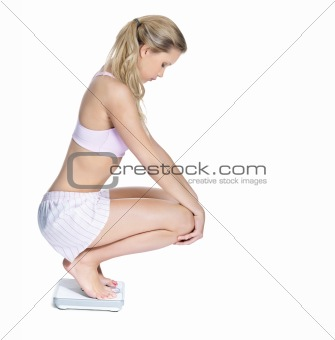Side view of a young female crouching on a weighing scale