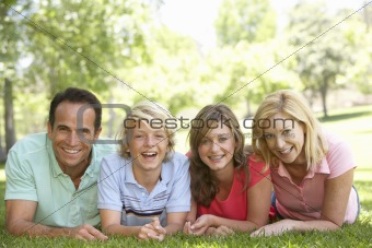 Couple And Their Teenage Children Lying On Grass
