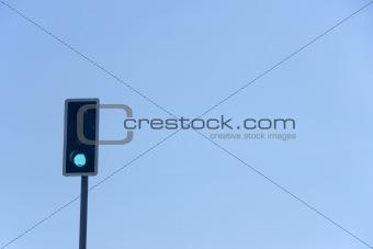 Green Traffic Light Against A Blue Sky