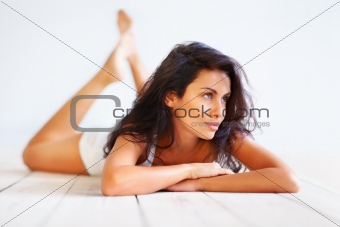 Brunette lying on wooden floor