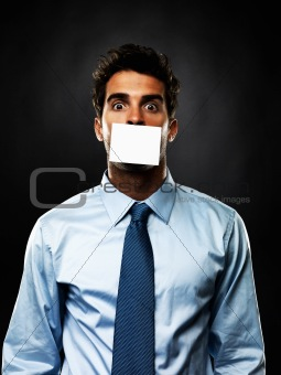 Portrait of shocked business man with paper covering his mouth