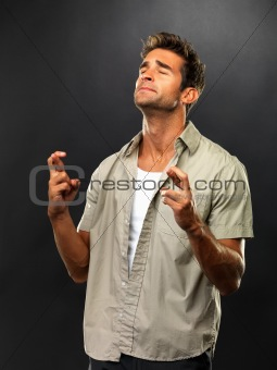 Young man with eyes closed crossing his fingers