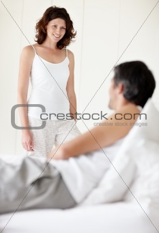 Pretty woman standing in bedroom with her husband