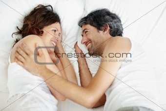 Middle aged couple lying on bed together smiling