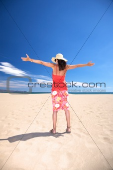 greeting woman with straw hat at beach