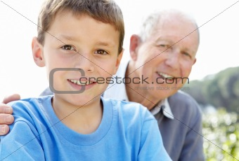 Closeup portrait of a little boy smiling with his grandfather