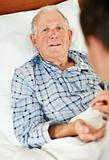 Portrait of an elderly man taking pill from the doctor