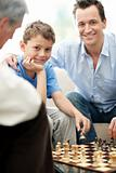 Father and son playing chess with a old man