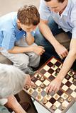 Family playing a game of chess together
