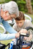 Senior man repairing a bicycle tyre with his grand son in a park
