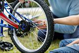 Two people fixing a bicycle tyre in a park