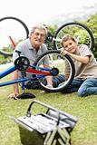 Little boy fixing a bicycle tyre with his grandfather