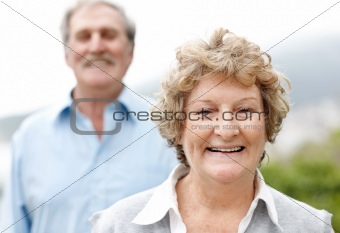 Happy old woman in front with a her husband