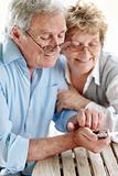 Senior couple sitting together using a mobile phone