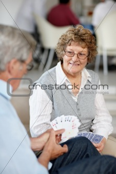 Couple enjoying playing cards together at a club