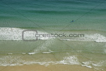 One lone man kayaking in the sea of Pedn vounder beach
